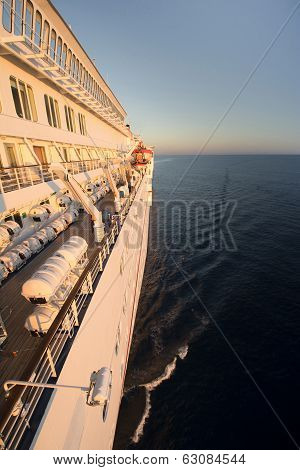 Side of a cruise ship bathed in early morning sun