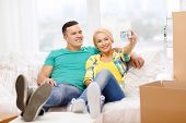 moving, home and couple concept - smiling couple relaxing on sofa taking picture with digital camera