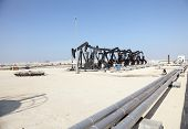 stock photo of bahrain  - Black oil pump jacks in the desert of Bahrain Middle East - JPG