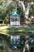 pic of gazebo  - A white traditional gazebo on the shore of a lake under spanish moss draped oak trees - JPG