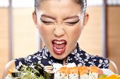 foto of sushi  - Beautiful sushi woman showing a plate of sushi - JPG