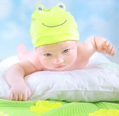 pic of baby frog  - Closeup portrait of cute little baby wearing funny frog costume and lying down on imagine floral field - JPG
