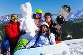 Four young people with snowboard and snowman