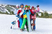 foto of snowboarding  - Group of happy smiling 2 men and 3 women with snowboards and skis standing on the mountains background - JPG