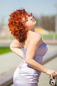 Gorgeous red-haired woman on a walk in the park  Young girl on the nature