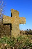 antique stone cross on meadow