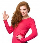 Young woman is showing OK sign, isolated over white