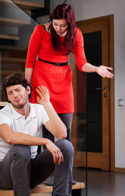 stock photo of fussy  - A wife standing over her husband complaining about his ignorance