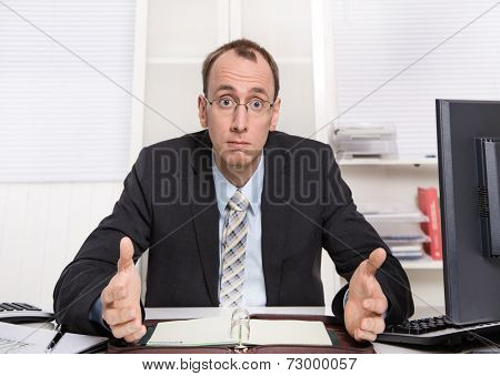Businessman is talking about savings and reduction of staff - sitting at desk with computer in suit and tie.
