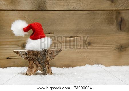 Wooden star with red santa hat on wooden background - handmade idea for a greeting card