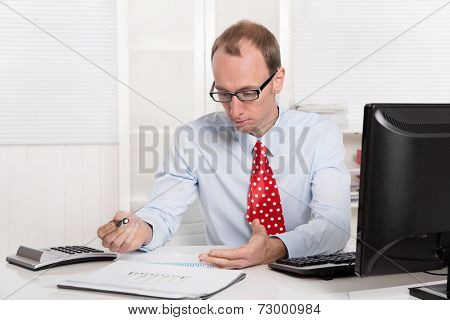 Quizzically engineer or specialist in shirt and tie sitting at desk