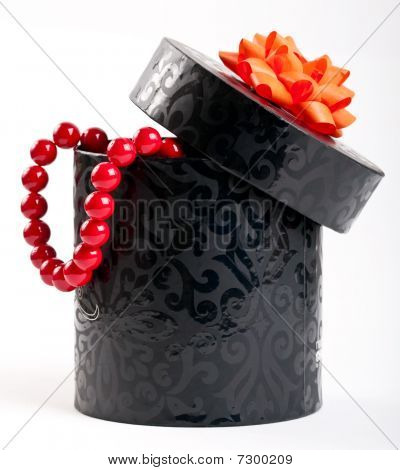 A Black Box Tied With A Orange Satin Ribbon Bow