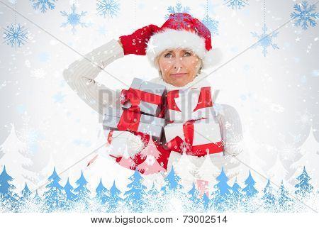 Festive woman scratching head and holding gifts against snowflakes and fir trees