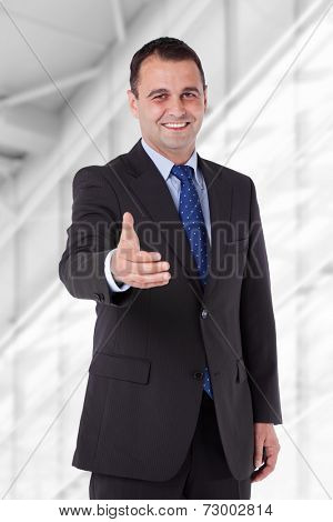 Businessman in a suit reaching hand for handshake. Isolated with work path.