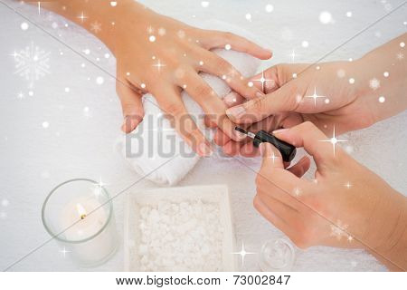 Nail technician painting customers nails against snow falling