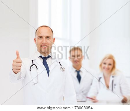 profession, teamwork, gesture and medicine concept - smiling male doctor with stethoscope in coat over group of medics showing thumbs up