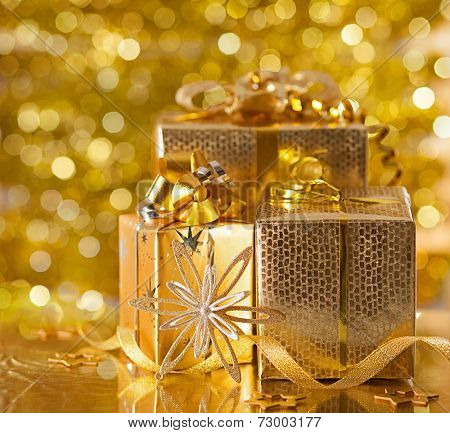 Gold Christmas gifts on background of defocused golden lights.