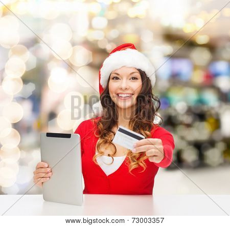 christmas, technology, shopping and people concept - smiling woman in santa helper hat with tablet pc computer and credit card over lights background