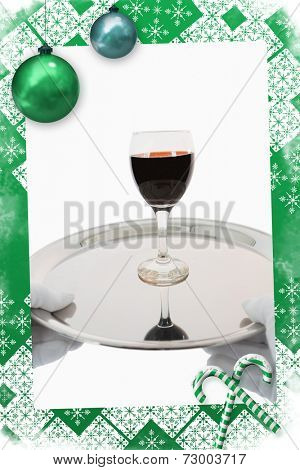 Waiter holding a glass of red wine against christmas frame