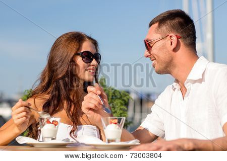 love, dating, people and food concept - smiling couple smiling couple wearing sunglasses eating dessert and looking to each other at cafe
