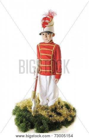 A handsome preschooler standing erect in his Christmas soldier uniform.  He's supports his rifle and is surrounded by green and gold garland.  On a white background.