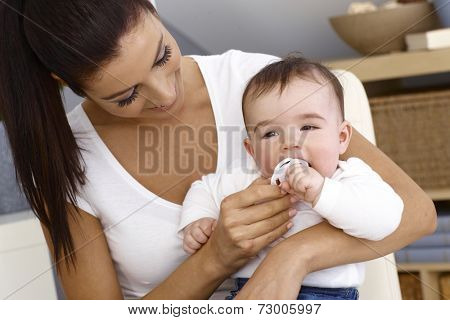 Happy mother holding baby boy in arms, embracing. Baby putting teat in mouth.