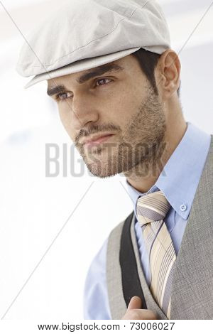 Closeup portrait of casual young man in hat, looking away.