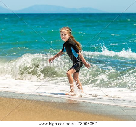 happy cute  girl playing in a wetsuit on the seashore