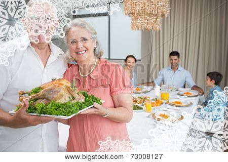 Grandparents holding chicken roast with family at dining table against snowflake frame