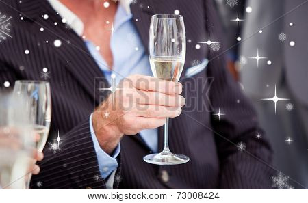 Close up of a senior businessman holding a glass of Champagne against snow falling