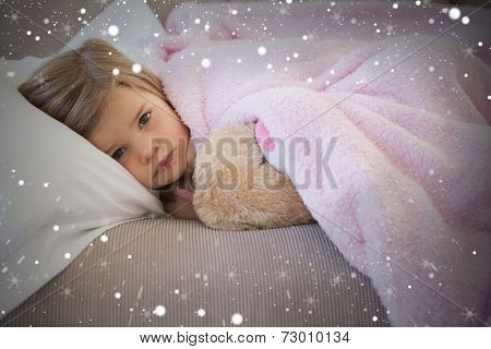 Composite image of young girl resting on sofa with stuffed toy against snow