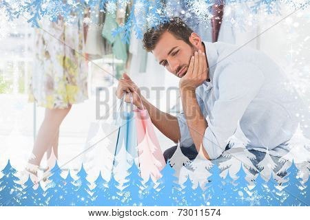 Bored man with shopping bags while woman by clothes rack against snow