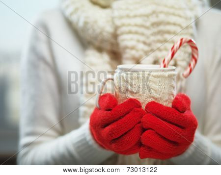 Woman holding winter cup close up on light background. Woman hands in woolen red gloves holding a co poster