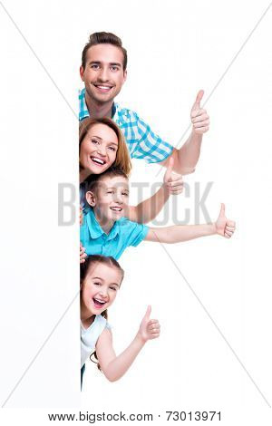 Young family with a banner showing the thumbs-up sign - isolated on a white background