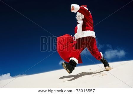 Santa Claus walking down a sand dune on a beach