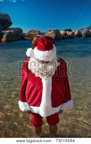 Out of context shot fo father Christmas at the ebach with his feet in the water relaxing