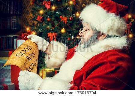 Santa Claus sitting in a room decorated for Christmas, and carefully read the list of good boys and girls. Christmastime.