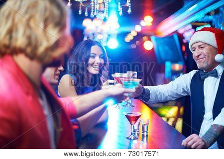 Portrait of boozing people toasting with cocktails at party