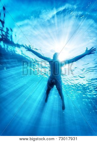 Sportive man swimming in the sea, active lifestyle, enjoying diving sport, refreshment in the cold water, summer vacation and travel concept
