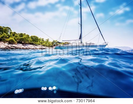 Luxury sailboat anchored near tropical island, amazing cruise along Greece, unforgettable summertime adventure, travel and tourism concept