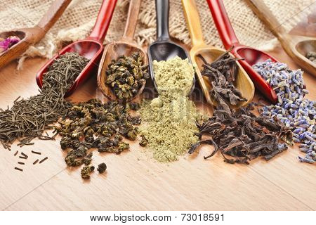 assortment of dry tea in spoon scoops close up  on wooden table background