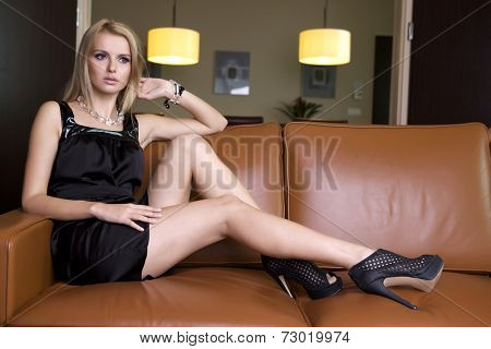 Young adult attractive and sensuality blonde woman in black elegance fashionable dress sitting on the couch