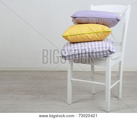 Bright pillows on chair in room