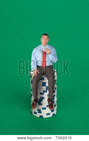 Businessman Sitting On Stack Of Poker Chips
