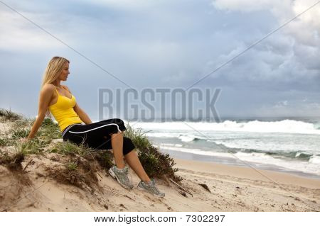 Young Woman Sitting By The Ocean