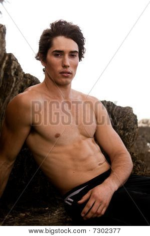 Shirtless Young Man By Rock Formation
