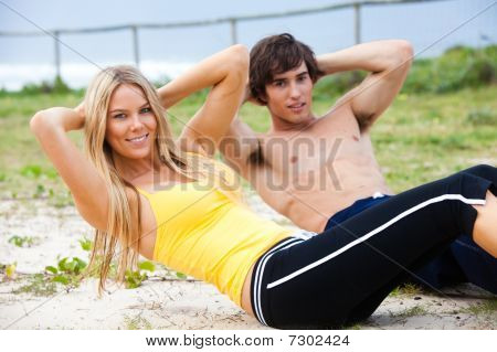 Young Couple Doing Sit-ups By The Ocean