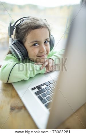 Portrait of cute girl listening to music on headphones while using laptop at home