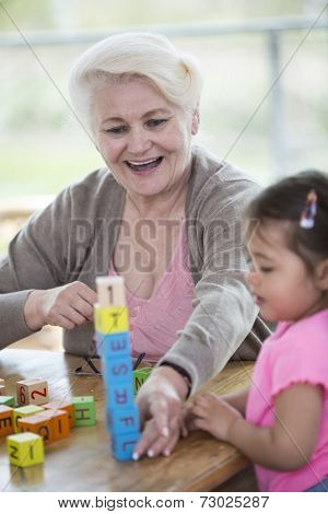Happy grandmother and granddaughter playing with alphabet blocks in house