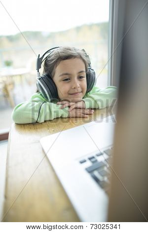 Cute little girl listening to music on headphones while using laptop at home